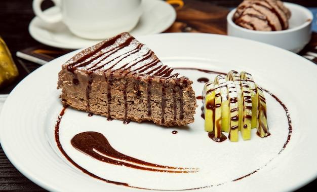 Кусочек торта с шоколадно-какао и яблочным пирогом с кусочками яблок и шоколадным соусом.