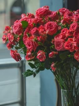Красные розы внутри прозрачной стеклянной вазы в комнате.
