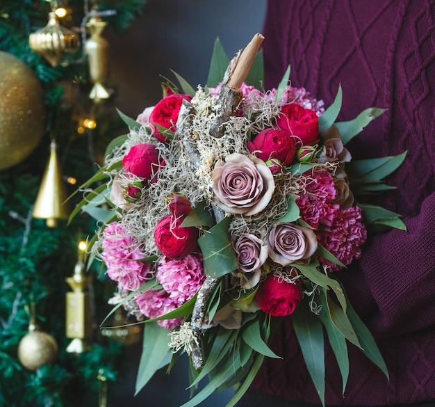 混合花の花束と冬の服装の男