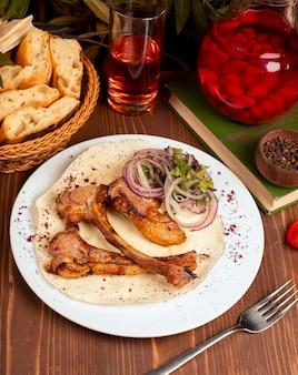 牛肉、子羊ラックのケバブ、タマネギのスライス、野菜、ハーブ、白プレートのラバッシュ添え