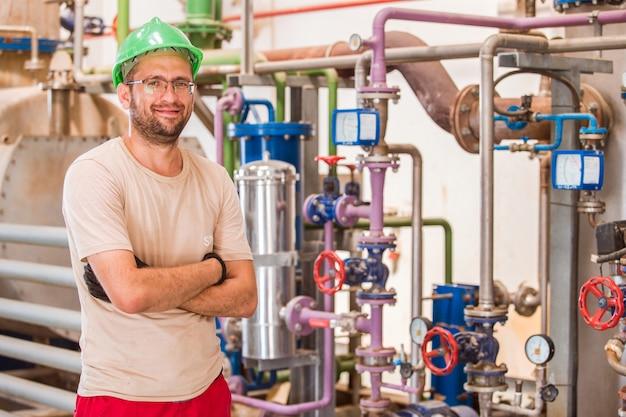 Промышленный рабочий позирует внутри фабрики с барами и трубами вокруг