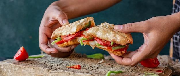 Мужчина резает руками сукук экмек, бутерброд с колбасой с курицей и смешанными продуктами