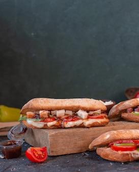 木の板にバゲットのパンでフェタチーズキューブとチキンサンドイッチ