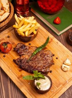 ビーフステーキ、フライドポテト、サワークリームマヨネーズソース、木の板にハーブ