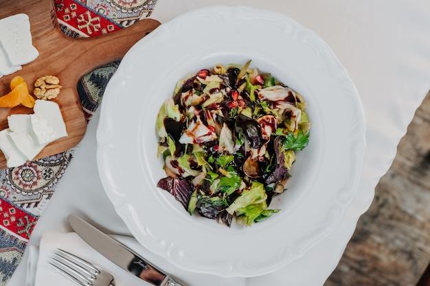 白い皿の中のバルサミコ酢と緑野菜のサラダ。
