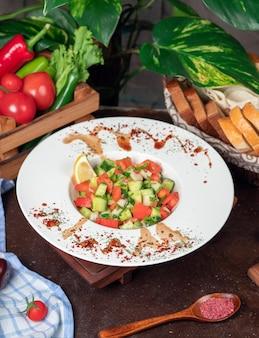 野菜、トマト、きゅうりのサラダ。スマークとレモンの白い皿の中の台所のテーブルの上のサラダ