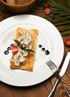マッシュトゥームは、一切れのパンに鶏のストロガノフをソテーした。木製のテーブルにカトラリーと装飾が施された白いプレートの前菜