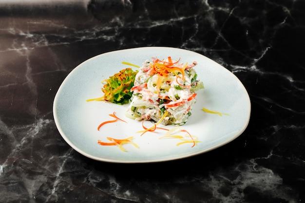 Салат смешанных ингридиентов внутри белой плиты на черном мраморе.