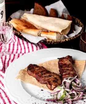 アゼルバイジャンの伝統的なケバブ、スマフ、タマネギ、グリーンサラダとラバッシュのバーベキュー。