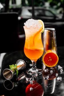 Свежий грейпфрутовый коктейль с кубиками льда и кусочками фруктов в стакане.