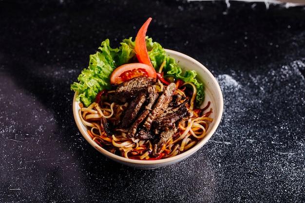 Китайская лапша внутри чаши с нарезанным стейком, ломтиками помидоров и листьями салата.
