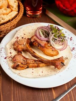 Шашлык из говядины, баранины, подается с ломтиками лука, овощами и зеленью, лаваш в белой тарелке.