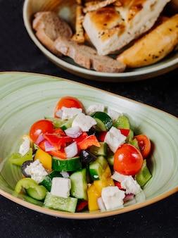 Смешанный овощной салат в зеленой тарелке.