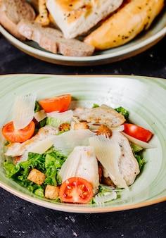 Салат цезарь с зеленью, помидорами и нарезанным пармезаном.