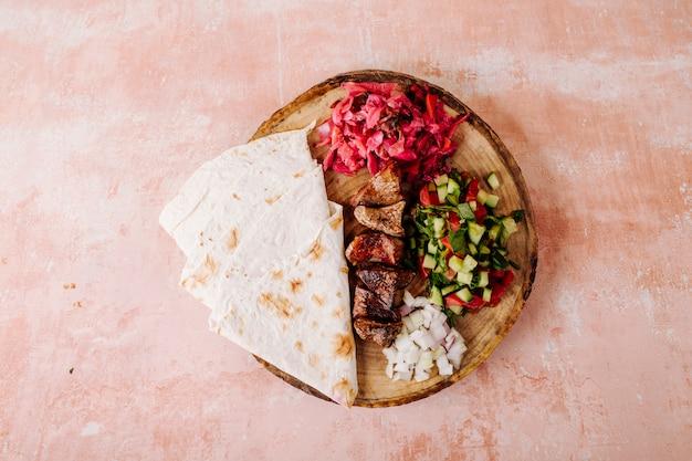 野菜のサラダと木の上のラヴァッシュ添えの肉のバーベキュー。