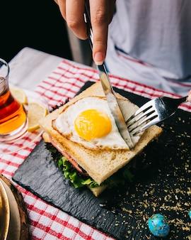 目玉焼きのサンドイッチをナイフとフォークで切る。