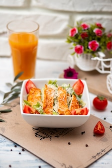 健康的なグリルチキンシーザーサラダ、チーズ、オレンジジュース、クルトン