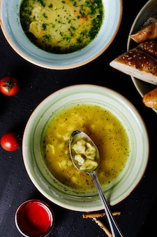 Макаронный суп с зеленью и ложкой внутри.