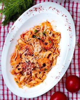 Итальянская паста в томатном соусе с нарезанным пармезаном.