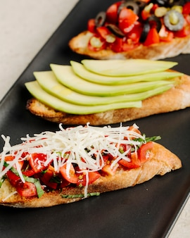 Три вида сэндвичей с помидорами, сыром, яблоками, оливками и другими ингредиентами.