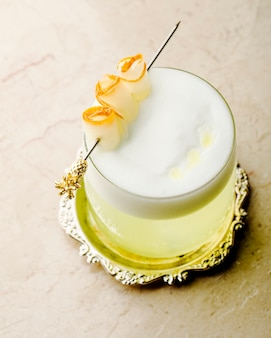 Стакан напитка с пеной внутри декоративного подноса.