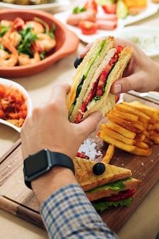 夕食のテーブルで手にクラブサンドイッチを持つ男。