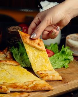 溶けたチーズとトルコのピデパンのスライスを取る女性。