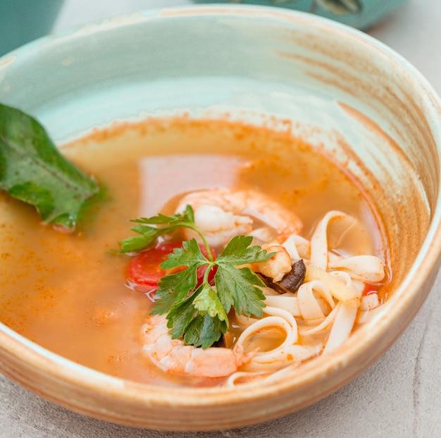 Суп с лапшой в томатном соусе с зеленью.