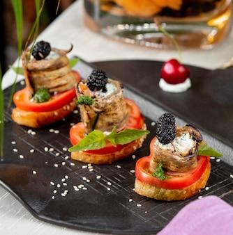 Крекеры с ломтиками помидоров, рулетиками из баклажанов и ягодами.