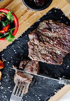 ナイフとフォークでステーキを切る。