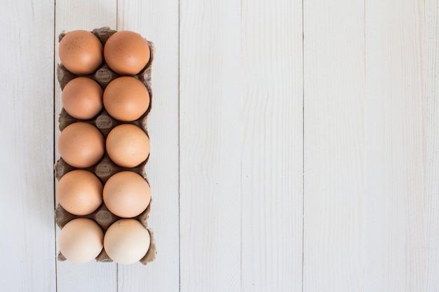 Свежие яйца в картонной упаковке на белой древесине