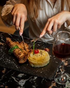 Женщина резки мяса стейк с картофелем в масках и стакан красного вина.