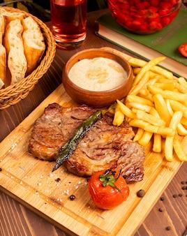 Стейк из говядины с картофелем фри, сметанным майонезным соусом и зеленью на деревянной тарелке