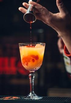 Добавляем красный сироп в апельсиновый коктейль.