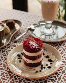 茶色のプレートの中にチョコレートチップを添えた赤いベルベットのケーキのスライス。