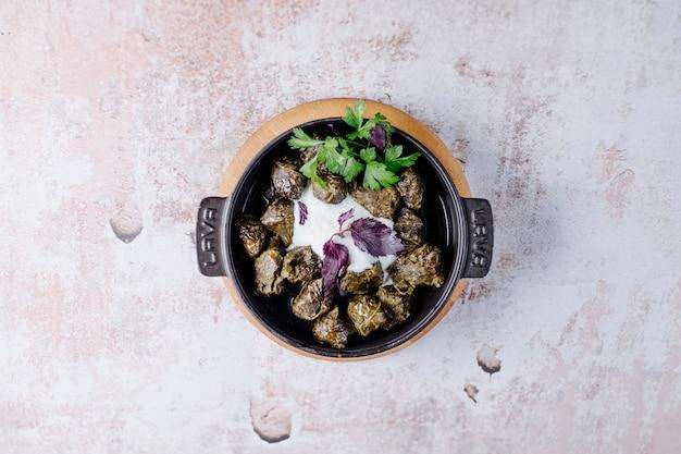 Азербайджанский ярпаг долмаси внутри черной сковороде с зеленью.