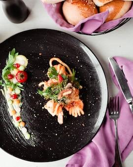 ホワイトソースとハーブの黒プレートの魚の切り身サラダ。