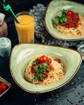 Спагетти в соусе болоньез, зелень и помидоры в зеленой тарелке и апельсиновый сок вокруг.