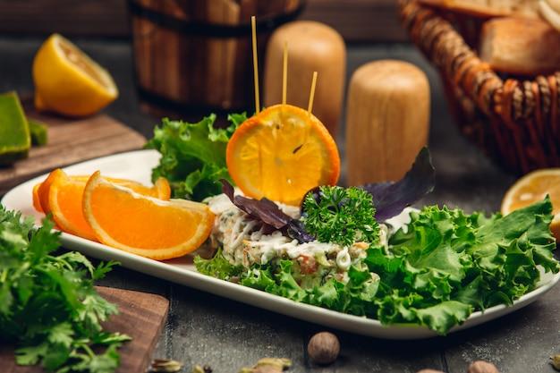 Русский столичный салат с листьями салата и дольками апельсина.