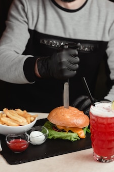 ハンバーガーからナイフを取り出す男。