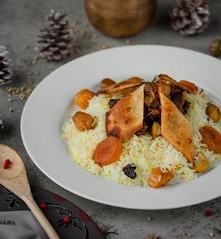 Рис украсить орехами и сухофруктами внутри белой тарелки.