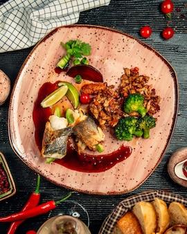 鶏ムネ肉の赤いプレートの中にナッツと緑のハーブとソースが入っています。