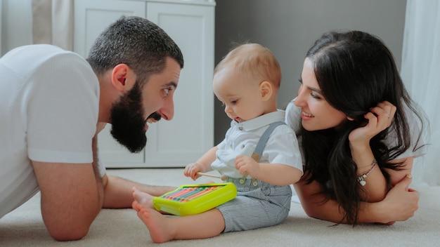 Родители играют с ребенком на полу.