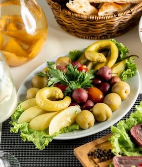 白い皿の中の野菜と果物のマリネ。
