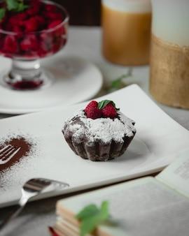 Шоколадный кекс с ванильным порошком и малиной.