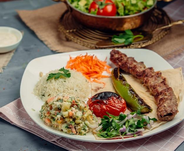 Кавказский люле кебаб с овощным салатом, жареными помидорами, перцем, зеленью и рисом.