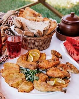 グリルチキンとポテトスライス、レモン、ハーブ、赤い飲み物とパンを添えて。