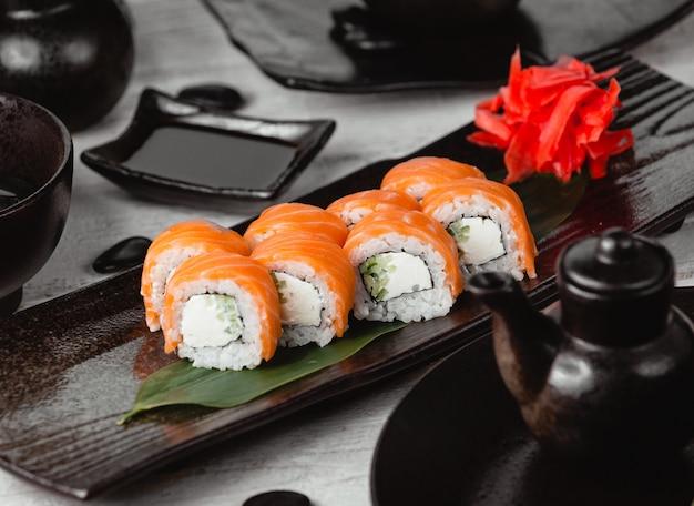 黒い皿の中にサーモンを巻いた巻き寿司。