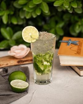 Лайм мохито с листьями мяты и кубиками льда в стакане.
