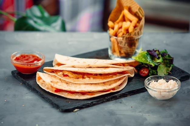 トマトソース、グリーンサラダ、フライドポテトとラバッシュのサンドイッチ。
